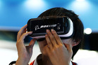 An attendee tries out a Samsung Electronics Gear VR virtual reality headset, powered by Oculus VR. Photo / Bloomberg