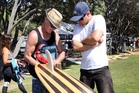 Mark Davy and Tim Boere discuss the finer points of a surfboard at the third running of The Cove Fish Fry. Photo / Tania Whyte