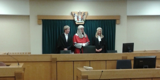 Demelza and Aaron Harvey flank Justice Timothy Brewer after they were admitted to the bar. Photo / Imran Ali