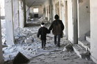 Two children walk through the corridors of a destroyed school in Eastern Ghouta, Syria. Photo / Save the Children, via AP
