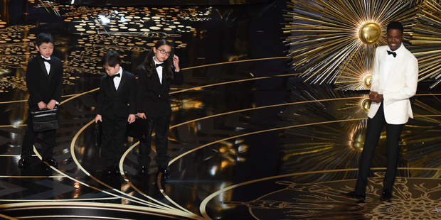 Actor Chris Rock presents Asian children representing accountants from PricewaterhouseCoopers on stage at this year's Oscars. Photo / Getty Images