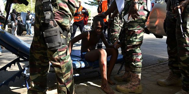 Soldiers stand around a young boy who was injured during an attack on the beach at the hotel Etoile du Sud in Grand Bassam. Photo / Getty