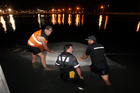 Volunteers from the Napier Coastguard work to bring the upturned boat ashore at Westshore, Napier. Photo / Hawkes Bay Today