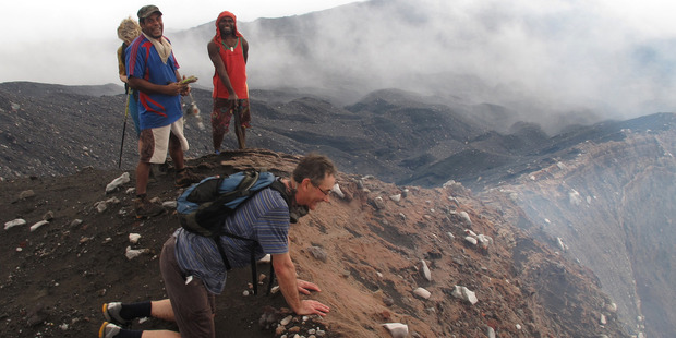 The professor takes a cautious peek over the edge o f Mt Marum's crater. Photo / Peter de Graaf