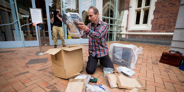 Loading Journalist Nicky Hager outside the Auckland High Court with what's left of his computer files and gear that was destroyed by police today. Photo / Dean Purcell