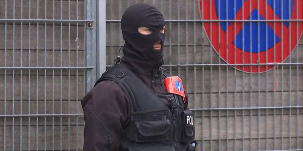 This framegrab taken from APTN shows an armed police officer during a raid in the Molenbeek neighborhood of Brussels, Belgium. Photo / AP