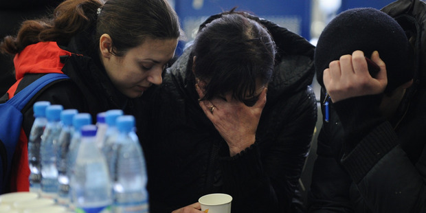 A Russian Emergency Situations Ministry employee, left, tries to comfort a relative of the plane crash victims. Photo / AP
