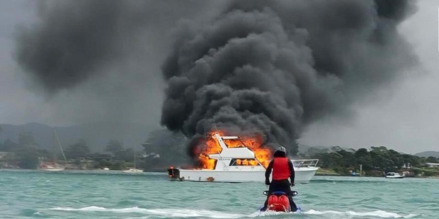 The 53-foot launch Mako fully engulfed in flames off the Marsden Cove Marina after the vessel's occupants, two adults and four children, were successfully rescued by police. PHOTO/SKI-NZ RIDERS