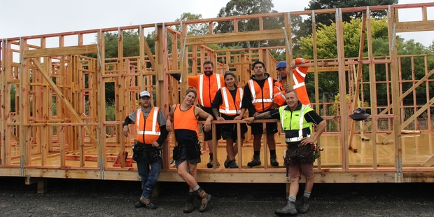 """Students on EIT's 10-month Level 3 carpentry course in Dannevirke. Seven students are currently undertaking the practical aspect of the course, building a three-bedroom, two-bathroom house at Tumu Timbers' yard which will be auctioned. Pictured, students with EIT tutor Campbell """"CJ"""" Johnston (front right). Photo / Christine McKay"""