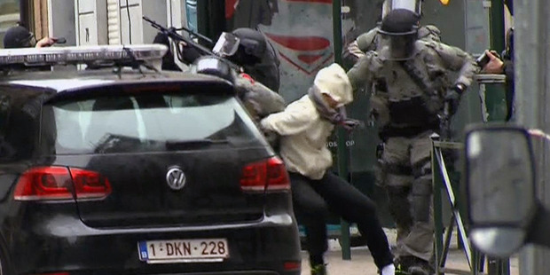 In this framegrab taken from VTM,  Salah Abdeslam, centre, is arrested by police and bundled into a police vehicle during a raid in Belgium. Photo / AP