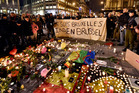 People holding a banner reading 'I am Brussels' behind flowers and candles to mourn for the victims at Place de la Bourse in the centre of Brussels. AP photo / Martin Meissner