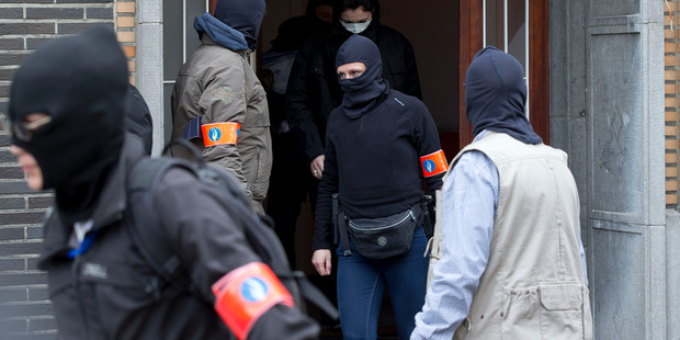 Belgium police leave after an investigating in a house in the Anderlecht neighbourhood of Brussels, Belgium. Photo / AP