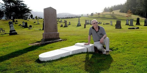 Bill Price surveys the damage to his late mother's headstone at West Taieri Cemetery. Photo / Linda Robertson