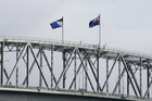 The existing New Zealand flag, right, flies alongside an alternative flag design on top of the Auckland Harbour Bridge. Photo / Getty Images