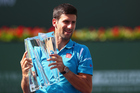 Novak Djokovic holds up the trophy after his win over Milos Raonic at Indian Wells. Photo / Getty Images