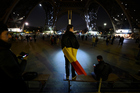 A boy wearing a Belgian flag stands under shows the Eiffel Tower in Paris illuminated in colours of the Belgian flag in tribute to the victims of terrorist attacks. Photo / Getty