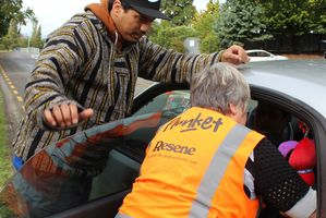 Damon Wharewhiti learns from Plunket's Helen Luke how to make his child's car seat safe for use at a checkpoint on Allen St in Dannevirke yesterday morning. Photo / Christine McKay
