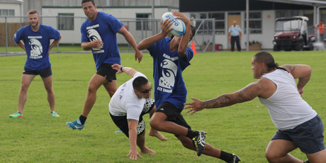 Son Hippolite, playing for the police team, slips between two inmates. Behind him are police officers Jamie Anderson (Paihia) and Matt Morris (Whangarei).