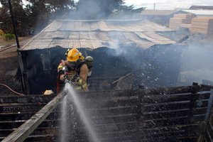 A firefighter hoses down a woodden stockyard fence ignited by radiant heat from a blaze that destroyed the nearby shed. PHOTO/NATHAN CROMBIE