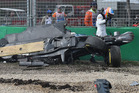 Fernando Alonso walks past his wrecked car after crashing during the Australian Grand Prix. Photo / AP