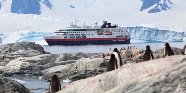 MS Fram navigates near Antartica's Half Moon Island, observed by a colony of Gentoo penguins. Photo / iStock