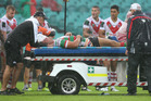 Sam Burgess of the Rabbitohs is taken from the field on a media cab . Photo / Getty