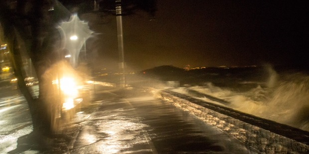 Water washes over a road in Auckland early this morning. Photo / Matthew Davison