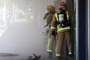 Pungent smoke pouring into Kaitaia's main street as firefighters using breathing apparatus prepare to enter Town and Country Food.