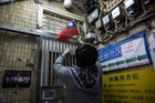 A man places a Taiwanese flag at the entrance to the closed Causeway Bay Books. The owner disappeared and emerged in China