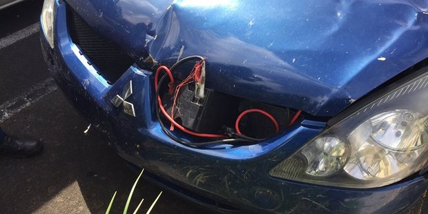 A home-made jump-starter kit was stuck on the Mitsubishi's dented and slightly detached bonnet. Photo / Facebook/Cambridge Police
