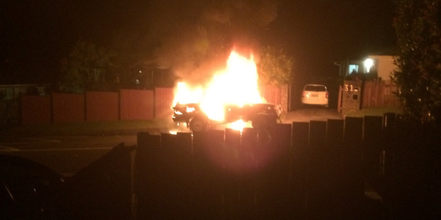 The car is well ablaze after crashing through the West Auckland fence. Photo / Julie Purcell
