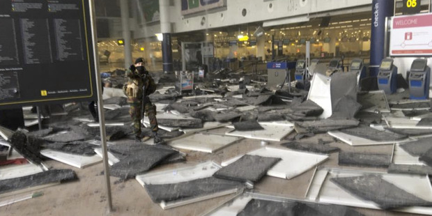 A member of the Belgian Special Forces stands in the departure hall of Brussels airport after two explosions. Photo / Twitter