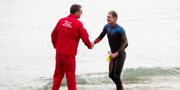 Rescue pilot James Tayler welcomes Swimmer Brent Foster who is the first swimmer home. Photo / Dean Purcell