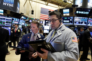 Traders Robert Charmack, left, and Michael Capolino work on the floor of the New York Stock Exchange. File photo / AP