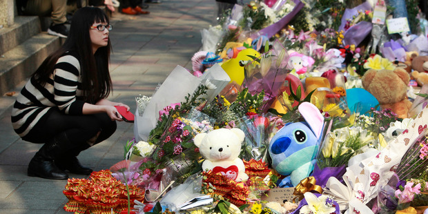 A woman visits a makeshift memorial for a girl who was attacked to death by a knife-wielding assailant outside a subway station in Taipei. Photo / AP