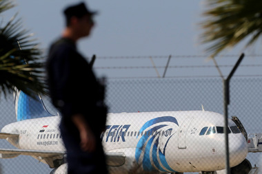 A police officers stands guard by the fence of the airport as a hijacked EgyptAir aircraft is seen after landing at Larnaca Airport in Cyprus. AP Photo/Petros Karadjias