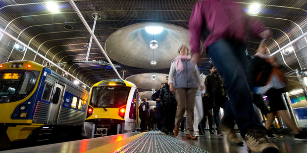 Morning commuters hurry to work on a train arriving late on the Southern Line at the Britomart Station, at approximately 9am. Photographed for an Auckland Transport train feature. 18 June 2015 New Zea