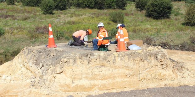 Archaeologists excavate the koiwi as kaitiaki Kawe Nikora (seated) supervises.