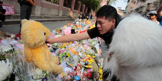 A man places a stuffed animal to a makeshift memorial offered with flowers for the 4-year-old girl who died after a random attack. Photo / AP