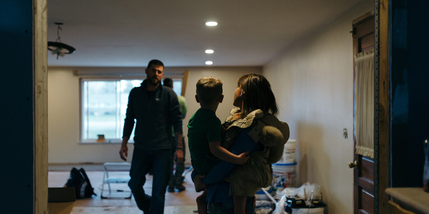 Annette Shattuck holds her son, Keaton, in their living room while her husband works on repairing the damage from when their home was raided in 2014. Photo by Ali Lapetina for The Washington Post