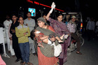 Pakistani relatives bring an injured child to the hospital in Lahore. Photo / Getty Images