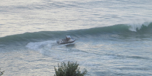 A strong wave threatens to flip the fishing boat over.