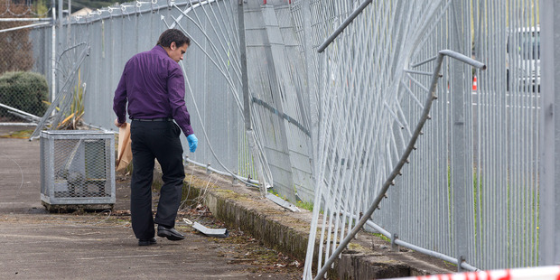 A police officer collects items of interest near the scene where 17 year old Ocean Poihaere Heke was found dead. Photo / Alan Gibson