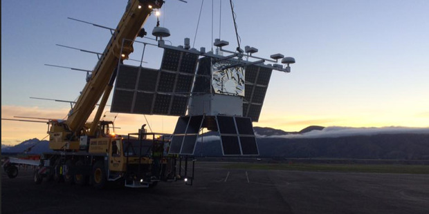 A crane takes the Compton Spectrometer and Imager back to the hangar at Wanaka Aerodrome. Photo / Supplied