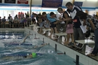 Timekeepers and supporters watch a close girls' backstroke final. Photos / Christine McKay
