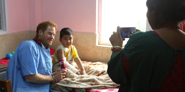 Prince Harry, left, poses for a photo with a young patient during a recent visit to the burn victim ward in Kanti Children Hospital in Kathmandu, Nepal. Photo / AP