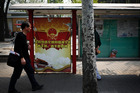 A man walks by a propaganda poster of China's Communist Party in Beijing. Photo / AP
