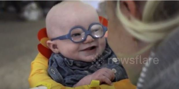 Baby Leopold's reaction is a huge smile for his mum, while others in the room can be heard gasping in delight. Photo / YouTube, Newsflare