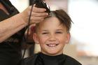 Oscar Maybury, 9, shaves his hair a second time for cancer. Photo/John Borren