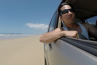 The writer drives down Teewah Beach, Sunshine Coast. Photo / Andrew Louis